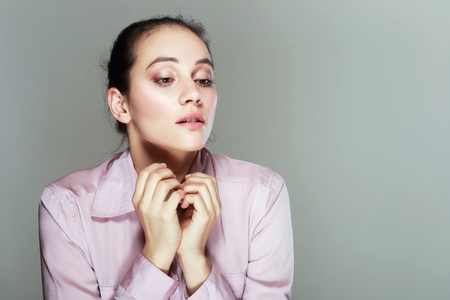 disoriented: Portrait of a young sad disoriented woman in pink blouse, she looks down Stock Photo