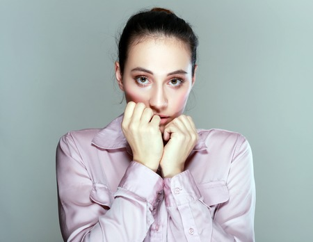 agape: Young woman reacting in shock and horror with her mouth agape and hands raised to her cheeks as she looks sideways to the left of the frame, over grey Stock Photo