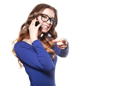 half length portrait: half length portrait of young smiling woman talking on the cellphone and pointing the finger at the camera isolated on white Stock Photo