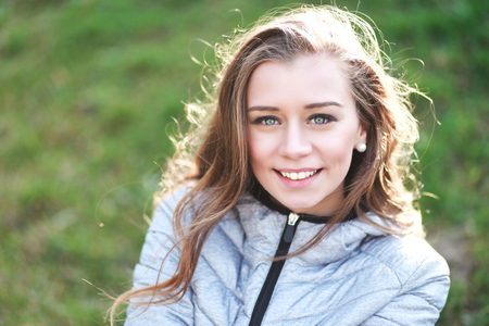 half length: half length portrait of young beautiful woman smiling and feeling happy on the nature looking at camera Stock Photo