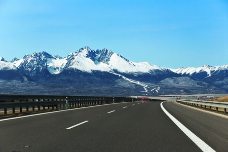 d1: High Tatras spring view with snow on mountainside and highway. Slovakia. D1 road, Strbske pleso. MARCH 2016