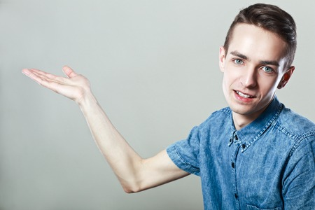 amiable: portrait of smiling young man presenting something isolated on grey background Stock Photo