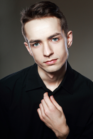 head tilted: close up portrait of nice young man looking at camera isolated on dark background Stock Photo