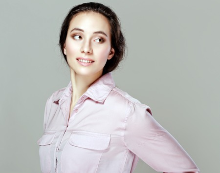 half length: half length portrait of pretty young woman looking sideways on neutral background