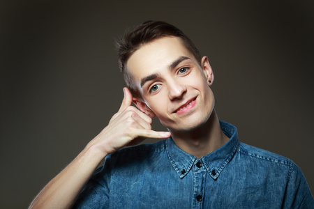 non verbal: Man playfully shows call me gesture. On a gray background Stock Photo