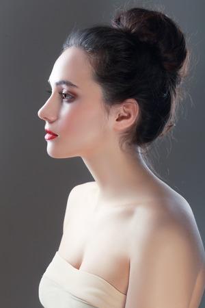 cabeza de mujer: Vista lateral del primer del perfil de la mujer joven y hermosa sobre fondo negro