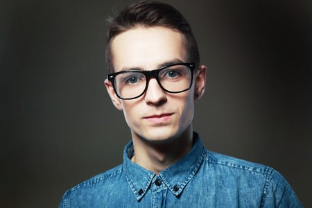 botan: Portrait of a serious young casual man over gray dark background. Man with eyewear looking, studio shot Stock Photo
