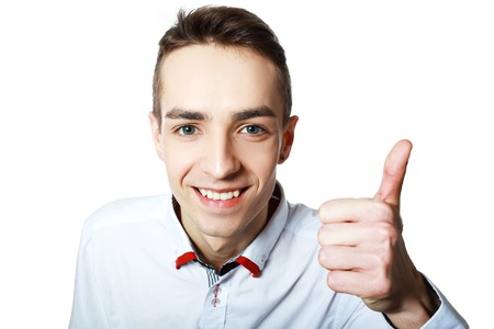 casuals: Young happy man with thumbs up sign in casuals isolated on white background.