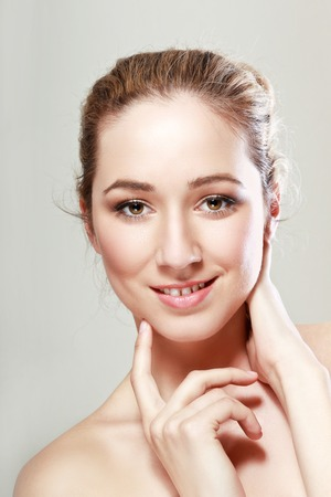 chin on hands: close up portrait of beautiful young woman with hands near her chin on neutral background