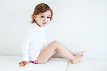 2 year old: Adorable 2 year old girl sitting barefoot at home Stock Photo