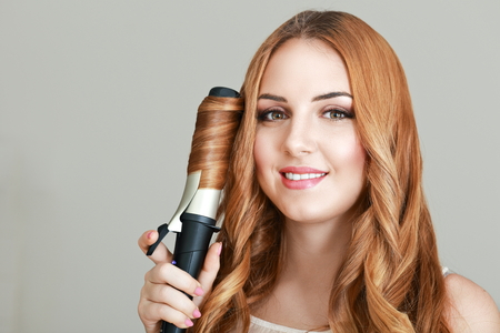 curling irons: close up portrait of beautiful young woman styling her hair with curling iron Stock Photo