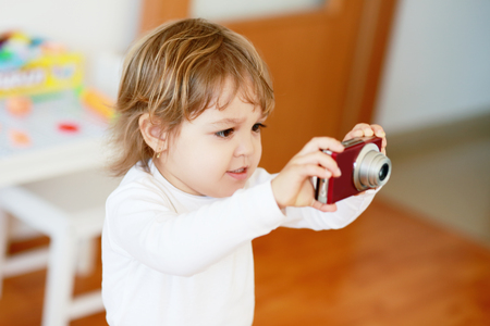 shootting: Little girl with compact photo camera