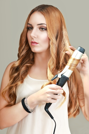 half length: half length portrait on neutral background with european beautiful young woman  curling her hair Stock Photo