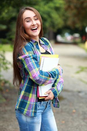 krásná dospívající studentka držet knihy v ruce as úsměvem Reklamní fotografie