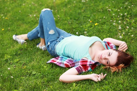 sleepiness: Young woman caucasian-asian resting laying on the grass in the park Stock Photo