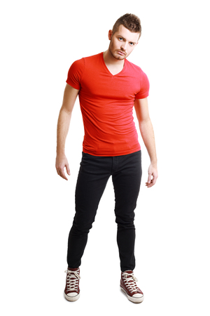 black pants: young male model posing in red shirt and black pants