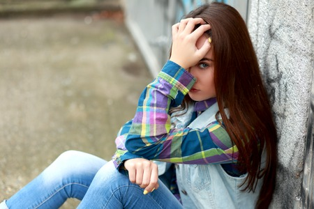 traumatized: sad lonely teenage girl sitting in urban environment. thinking of teenage problems