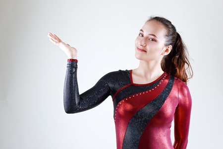 half length portrait of beautiful young gymnast representing herself on neutral background in photo studio