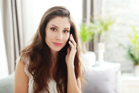 Smiling brunette sitting on her couch on a phone call at home in the living room
