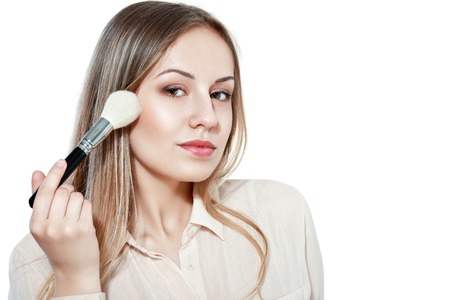 close up portrait of young woman with makeup brush isolated on white background in photo studio Stock Photo