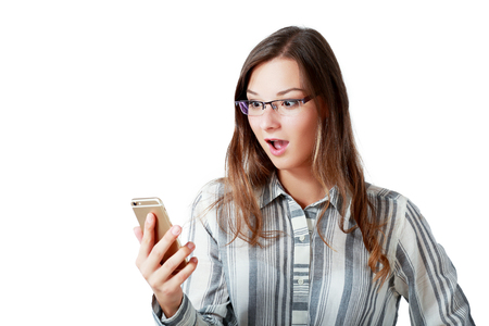 The young girl is holding a cell phone and looking at the screen with a surprised expression Stock Photo