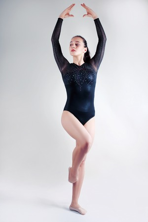 full length portrait of young graceful gymnast on neutral background in photostudio Stock Photo