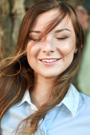upper half: close up portrait of beautiful young woman with wawing hair in the wind Stock Photo