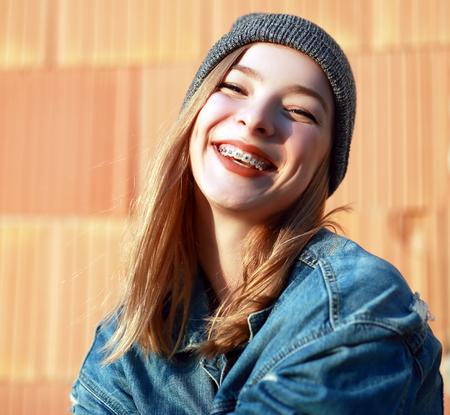 mooi blond tienermeisje met steunen op haar tanden glimlachen