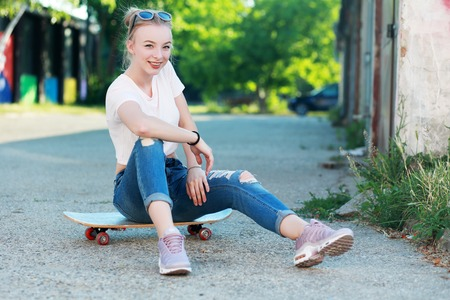 artsy: Beautiful young woman with skateboard Fashion style Urban background Stock Photo