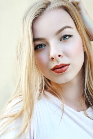 cabeza de mujer: close up portrait of pretty young girl with beautiful blue eyes looking at camera on the street