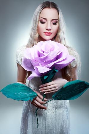 dark elf: Beautiful young woman with big paper flower in her hands over dark background Stock Photo