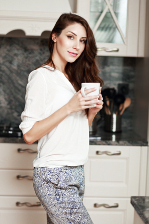 half length portrait: half length portrait of young woman standing on the kitchen with warm cup of coffee