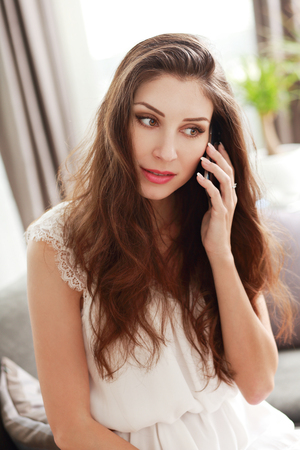 half length portrait: half length portrait of young woman talking on the cellphone in the apartment Stock Photo