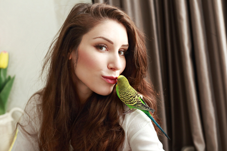 half length portrait: half length portrait of young woman with cute parrot on her shoulder giving her a kiss