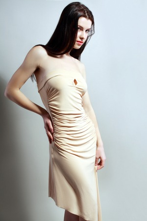 Portrait of beautiful woman in beige dress posing at studio