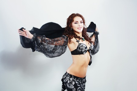 harem: Beautiful Arabic belly dancer harem woman in black with silver dressdancing arms in air