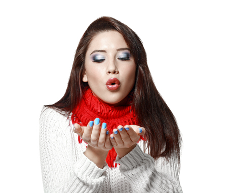 warm cloth: portrait of beautiful young  woman in sweater and red scarf blowing in her hands isolated on white in photostudio Stock Photo