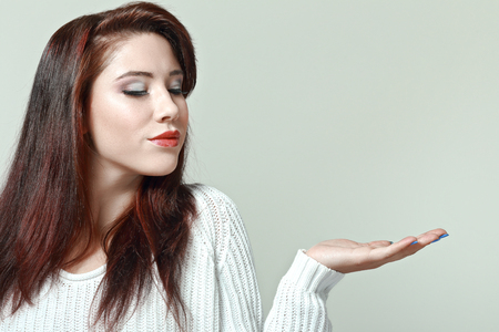 portrait of young beautiful woman with open palm posing in photostudio on neutral background
