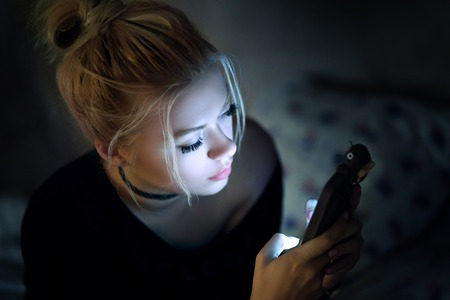 overuse: Woman using smartphone on bed at night
