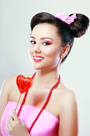 Beautiful Pinup Pop-Art Candy Girl in pink paper dress holding flower shaped lollipop, neat retouched image.
