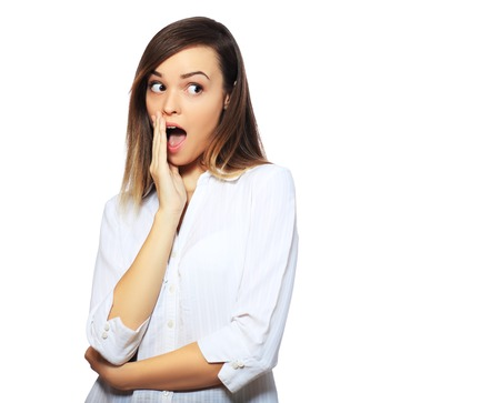 18's: Surprised excited woman screaming amazed in joy. Beautiful young woman isolated on white background in casual white shirt. Asian Caucasian multiracial female model in her 18s
