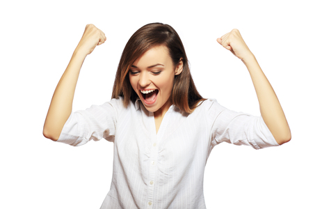 Winner business woman with her hands raised excited looking up