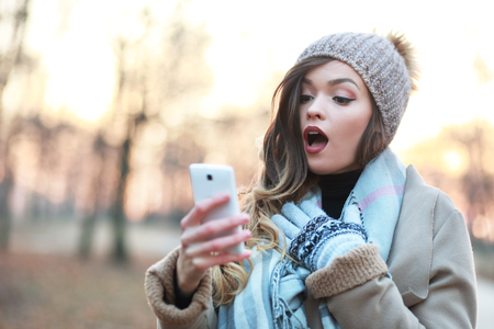 shocked girl looking at smartphone screen amazed and excited Stock Photo