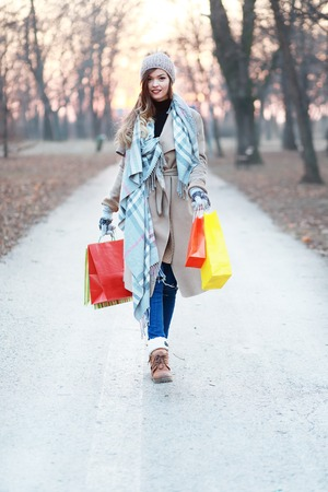 good weather: beautiful girl walking with shopping bags toward you on the road, space for your text