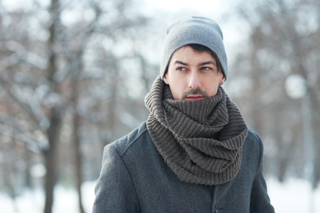 Outdoor portrait of smiling handsome man in coat and scurf. Casual winter fashion Stock Photo