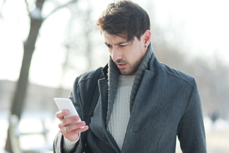 disbelief: man looking on his smartphone unhappily with disbelief at the winter snowy park