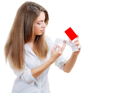 compulsive: Stock image of surprised young woman looking at sale ticket after shopping too much and overspending holding credit card in another hand Stock Photo