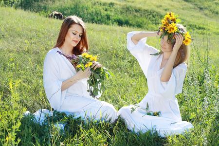 zwei schöne junge Frauen, die Blumen im Sommerfeld garlanding