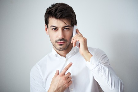 portrait of young man in white shirt talking on the cellphone posing next to color background looking at camera