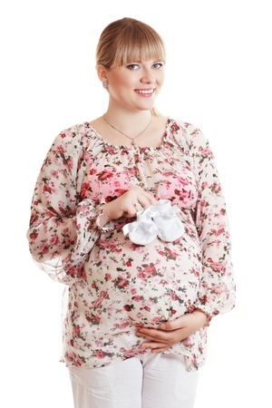 beautiful pregnant woman smilimg holding in arms babys bootees isolated on white background in photostudio
